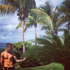 A shirtless Justin Bieber admiring the plant thinking Can i smoke this
